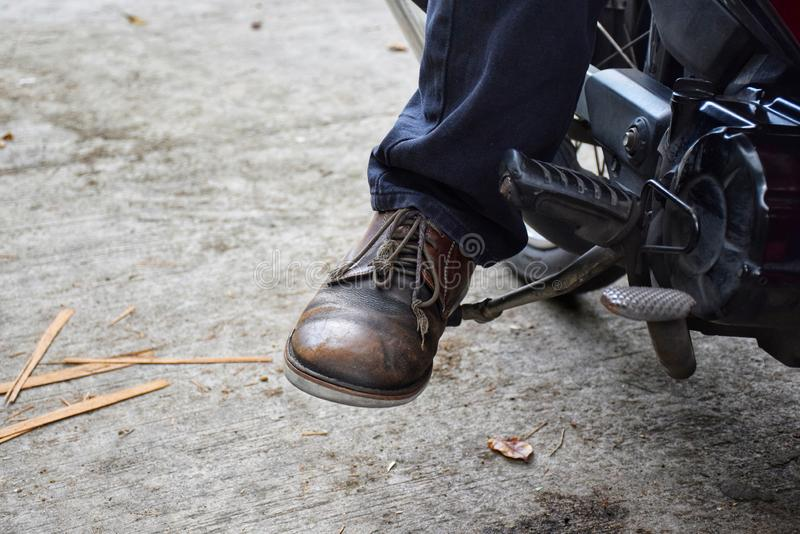Sit on your motorcycle and Start the engine with foot start rod or Kick starter stock photos