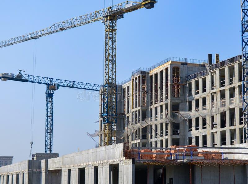 Site concret de construction de bâtiments avec des grues en ciel bleu photos libres de droits