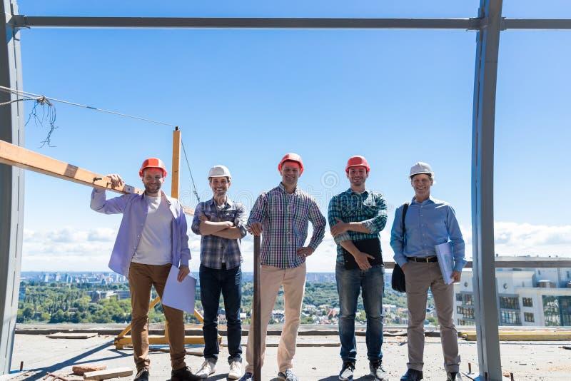 Site de Team Of Builders On Costruction, association de sourire heureuse de Group In Hardhat d'agent de maîtrise dehors et concep photographie stock libre de droits