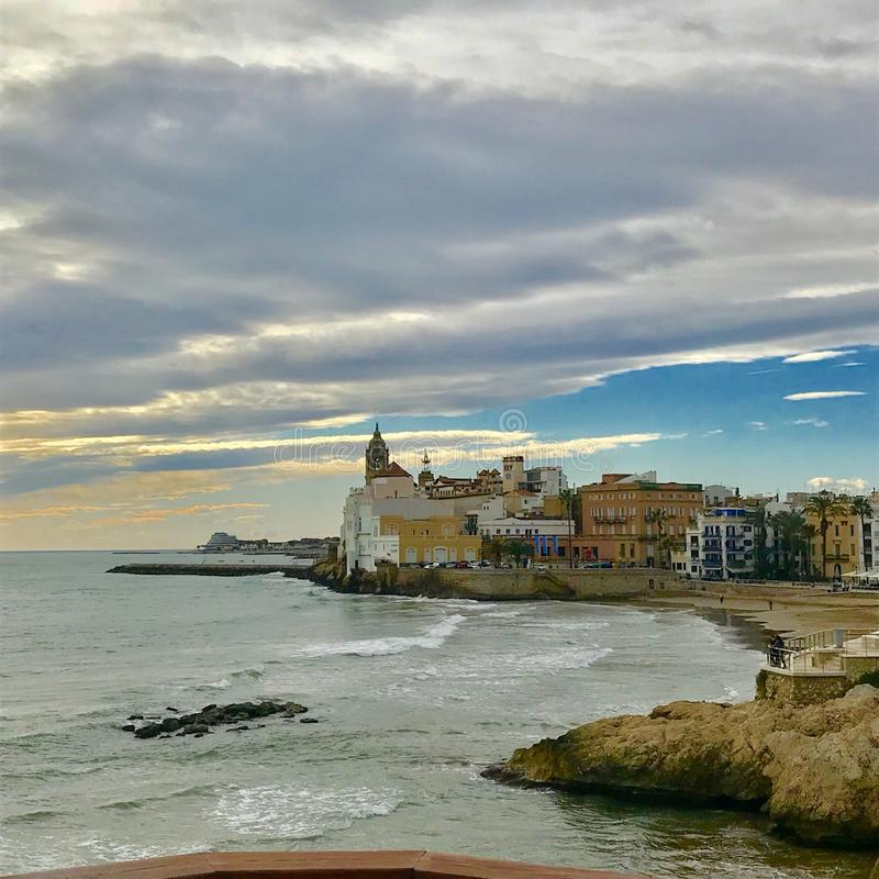 Sitges. Sea lansdscape of the Sitges town in the spanish mediterranean coast in a winter sunny day. There are some waves and buildings as the old church stock images