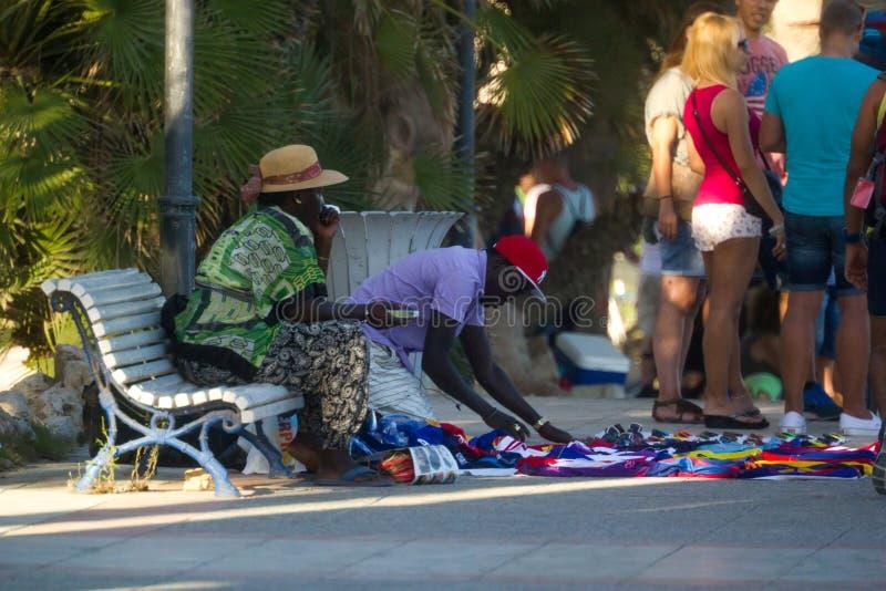 Sitges, Spanje - 21 Augustus 2016: Afrikanen treffen voorbereidingen om vervalste goederen op promenade van Sitges te verkopen royalty-vrije stock afbeeldingen