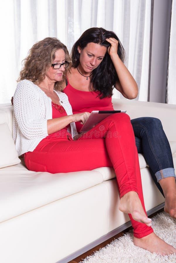 sitiing在长沙发和看在片剂的两名可爱的妇女 库存图片