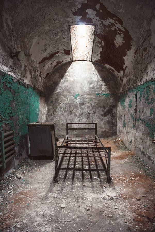 Sitio abandonado de celda de prisión con las paredes oxidadas viejas del marco y de la peladura de la cama fotos de archivo libres de regalías
