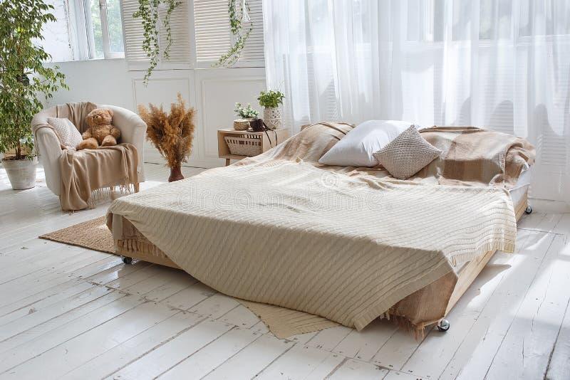 Sitio acogedor del desv?n brillante elegante con la cama matrimonial, la butaca, las plantas verdes, las cortinas, las paredes de foto de archivo