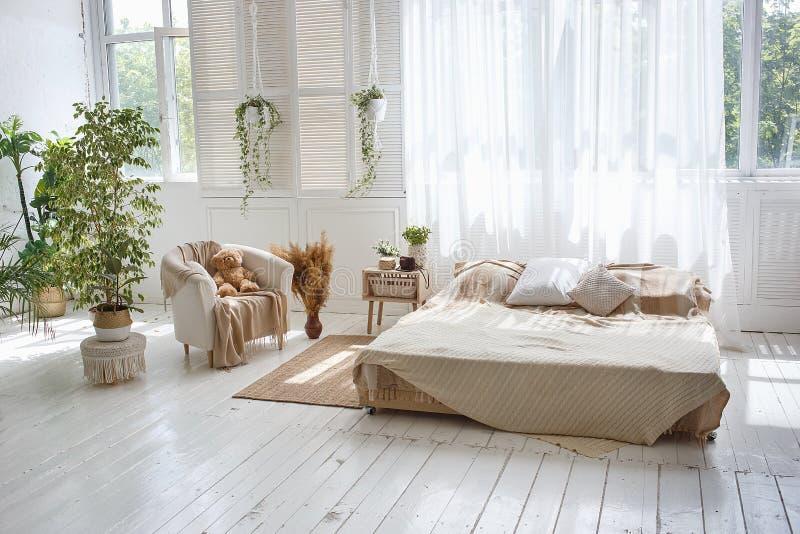 Sitio acogedor del desv?n brillante elegante con la cama matrimonial, la butaca, las plantas verdes, las cortinas, las paredes de foto de archivo libre de regalías