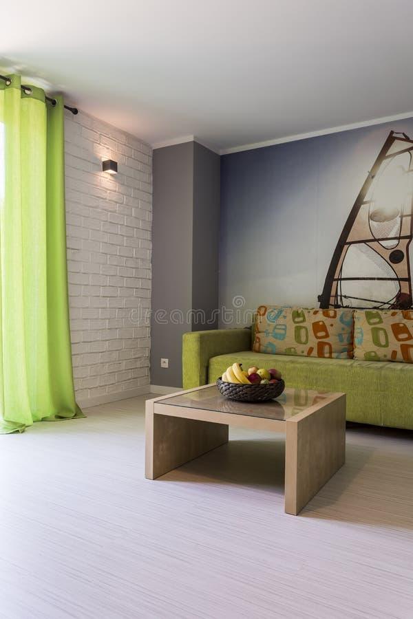 Sitio brillante con el sofá verde fotos de archivo
