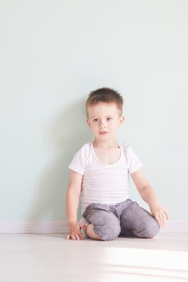 Sitio brillante muchacho feliz que juega en el piso Un muchacho en una camiseta blanca imagen de archivo libre de regalías