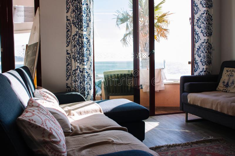 Sitio cómodo con el sofá y balcón con la opinión del mar Interior acogedor del apartamento Sala de estar con la decoración y mueb fotos de archivo libres de regalías