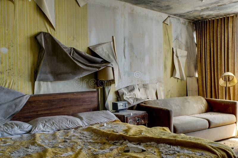 Sitio de alojamiento intacto con la cama y los muebles - hotel abandonado fotos de archivo