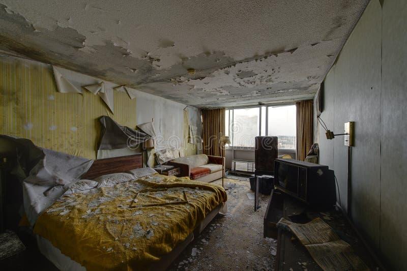 Sitio de alojamiento intacto con la cama y los muebles - hotel abandonado fotos de archivo libres de regalías