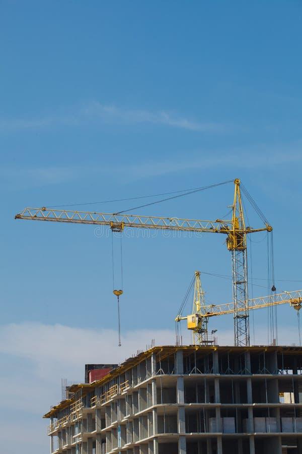 Sitio de la construcción de la grúa y de edificios contra el cielo azul fotos de archivo