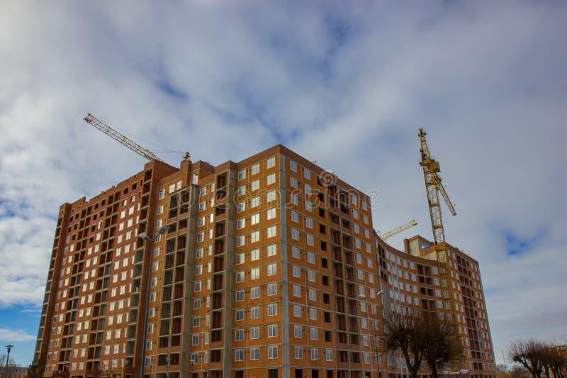 Sitio de la construcción de la grúa y de edificios contra el cielo azul fotografía de archivo