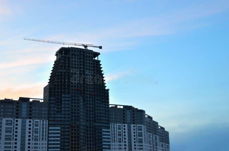 Sitio de la construcción de la grúa y de edificios contra el cielo azul con la cartelera blanca en blanco para el anuncio en la c fotografía de archivo libre de regalías