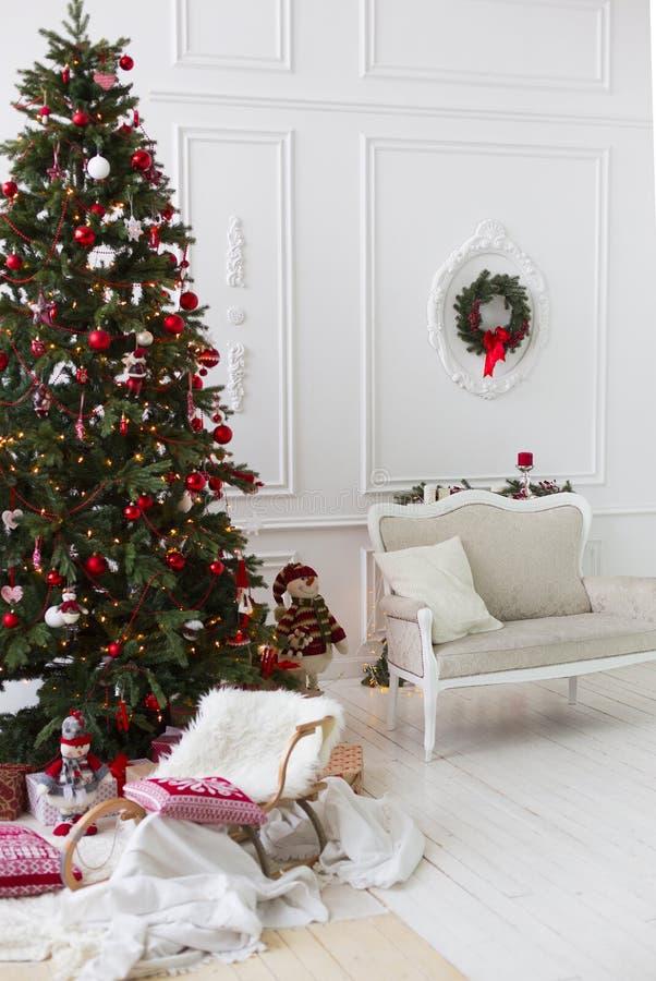 Sitio de la Navidad o de Año Nuevo con el árbol de navidad vestido con las bolas y las velas rojas, trineo de madera decorativo d imagen de archivo libre de regalías