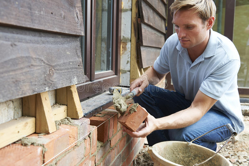 Sitio de Laying Bricks On del trabajador de construcción imagen de archivo libre de regalías