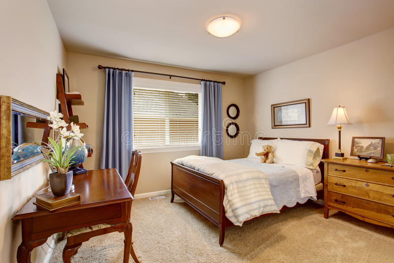 Sitio de los niños del beige con el sistema de madera de los muebles, las cortinas azules y el lecho pelado imagen de archivo libre de regalías