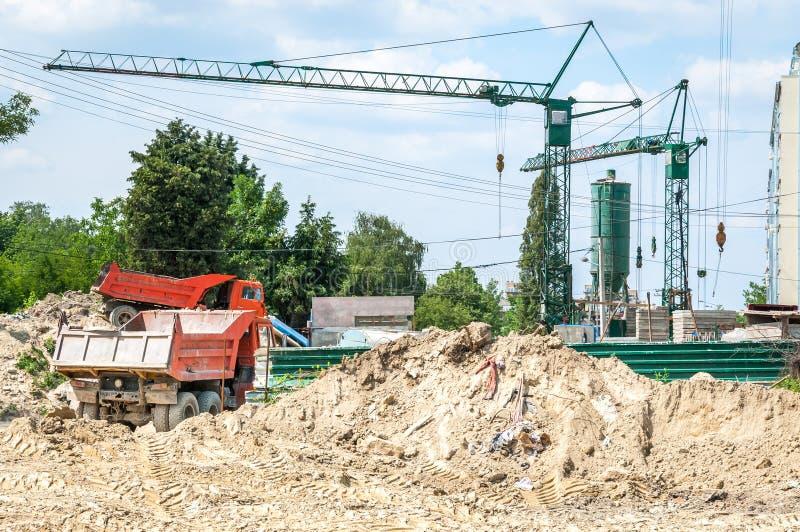 Sitio de tierra de la excavación con los camiones de volquete y las grúas de construcción pesados en la nueva preparación del ter fotos de archivo libres de regalías