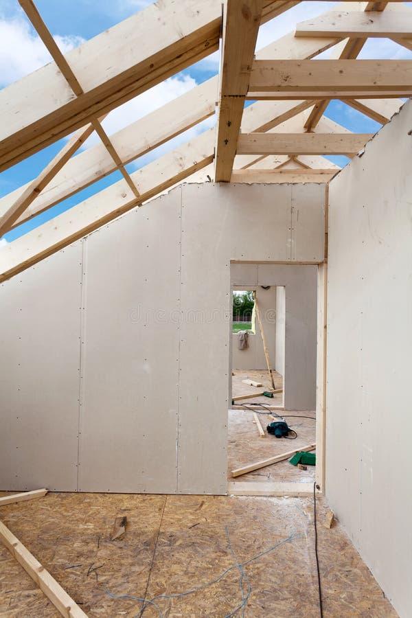 Sitio del ático bajo construcción con los tableros de yeso del yeso Construcción de la techumbre interior Construcción de madera  imagen de archivo
