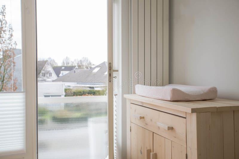 Sitio del bebé con diseño moderno cambiante de la estera y la ventana abierta imagen de archivo libre de regalías