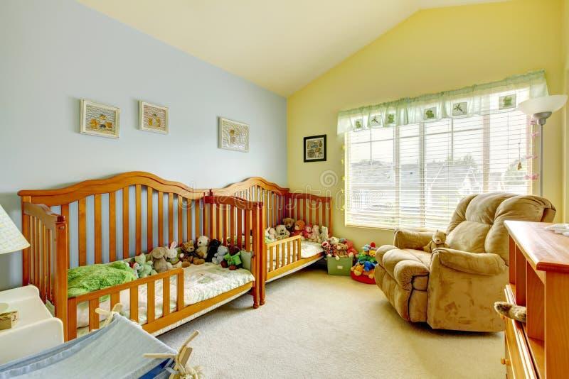 Sitio del cuarto de niños con dos pesebres para los gemelos y las porciones de juguetes foto de archivo