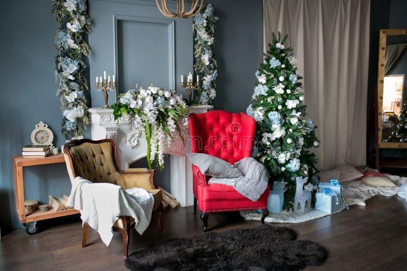 sitio del Desván-estilo con una butaca roja y marrón, una chimenea blanca con las flores, adornadas para la Navidad Regalos en la fotos de archivo