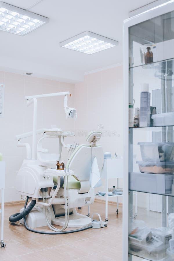 Sitio dental con la silla verde moderna, tono blanco del tratamiento Silla ortodóntica en pequeño gabinete de la estomatología Of imagen de archivo