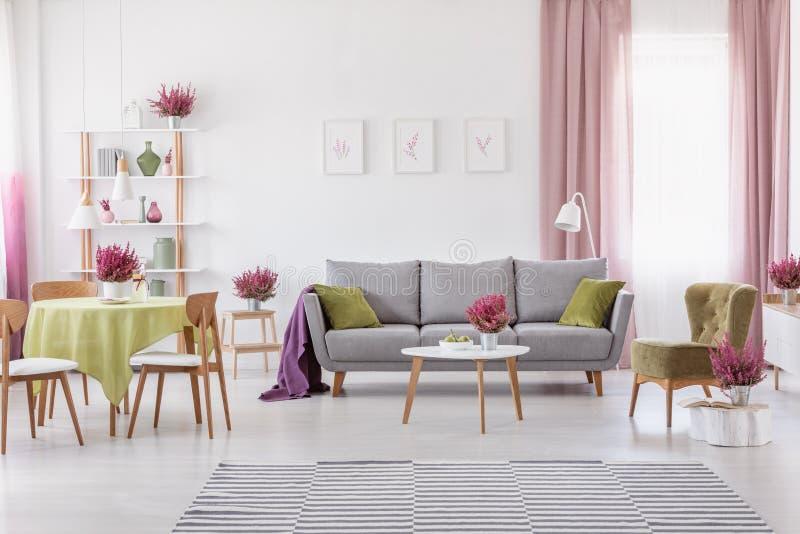 Sitio diario elegante con la mesa redonda con las sillas de madera y el sofá gris con las almohadas verdes verdes olivas, butaca  foto de archivo