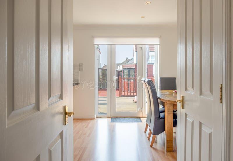 Sitio escocés moderno de Dinning de la cocina con la tabla de roble y sillas en Coloirs pintado blanco limpio que mira sobre las  fotos de archivo