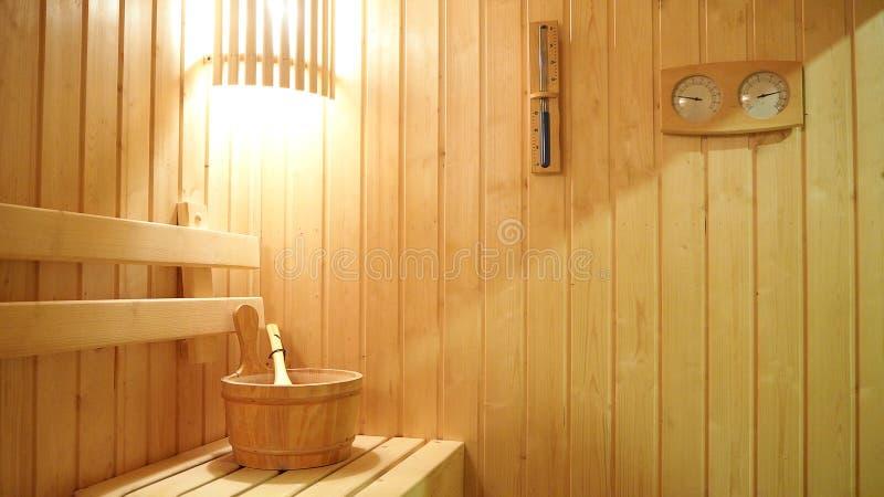 Sitio interior de la sauna Sauna de madera clásica con la luz, el termómetro y el reloj de arena en la pared Relájese en sauna ca imagen de archivo