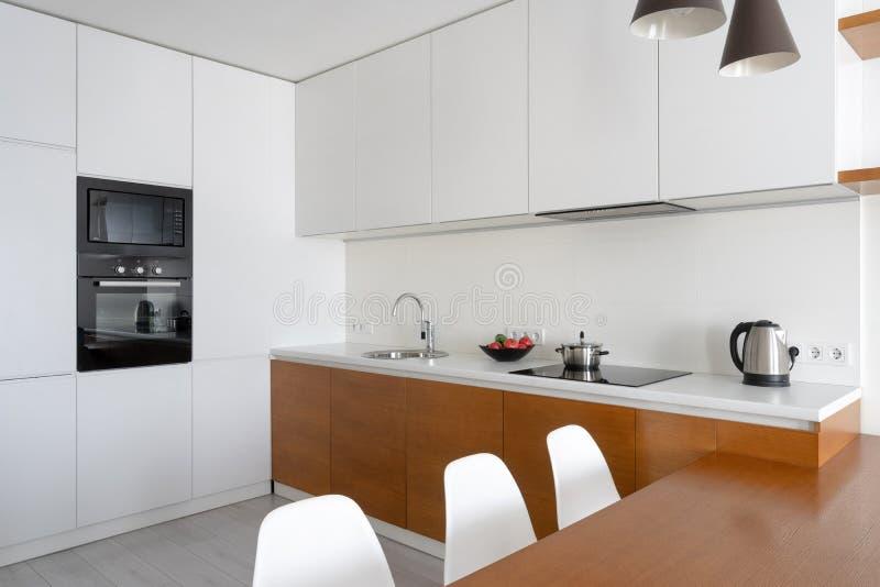 Sitio moderno blanco de la cocina con el interior moderno en plano acogedor fotografía de archivo
