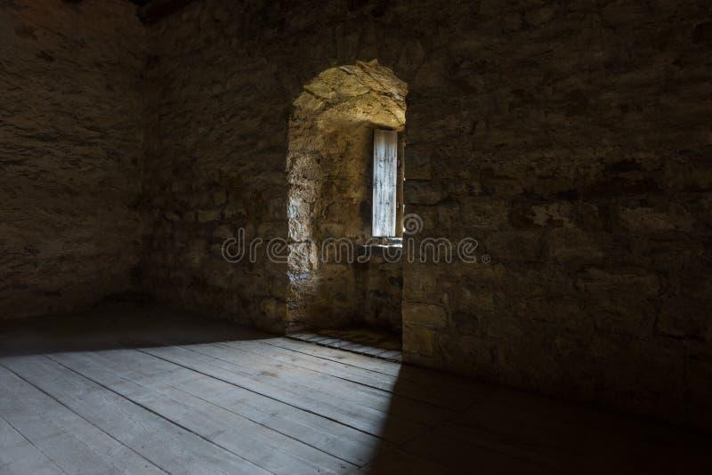 Sitio oscuro con las paredes de piedra y la ventana imagen de archivo