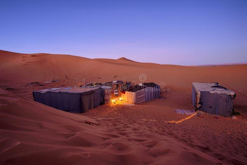 Sitio para acampar turístico del desierto con las tiendas detrás de las dunas de arena imagenes de archivo