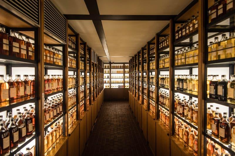 Sitio por completo de los gabinetes del whisky que almacenan diversos tipos de whisky fotos de archivo