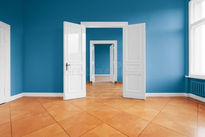 Sitio vacío del apartamento con las paredes y el piso de entarimado azules imágenes de archivo libres de regalías