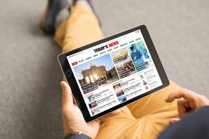 Sitio web de las noticias de la lectura del hombre en la tableta Se compone todo el contenido foto de archivo libre de regalías