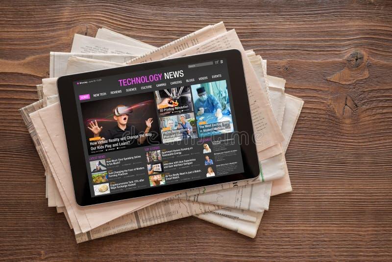 Sitio web de las noticias de la tecnología en la tableta en la pila de periódicos imagen de archivo libre de regalías