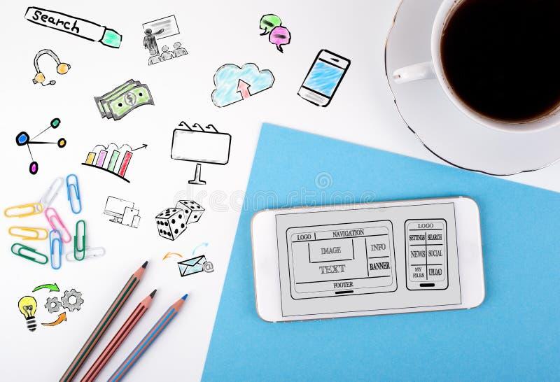Sitio web y concepto móvil del desarrollo del app Teléfono móvil y taza de café en un escritorio de oficina blanco imagen de archivo