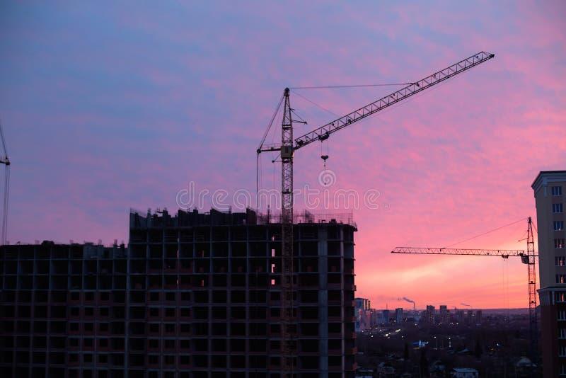 Sitio y grúa de la construcción de viviendas en la ciudad en salida del sol imágenes de archivo libres de regalías