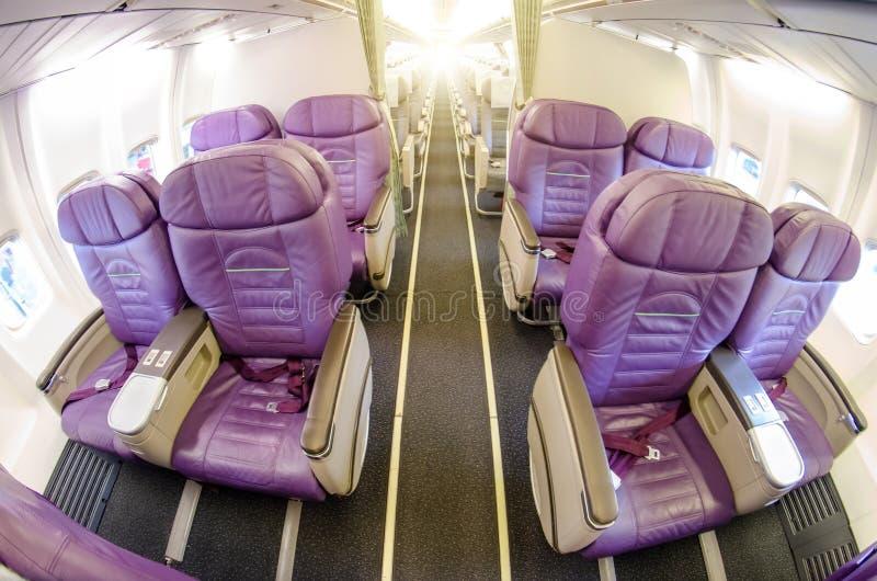 Sitios vacíos en asientos de la clase de negocios de un aeroplano del pasajero Paso de la perspectiva en la cabina foto de archivo libre de regalías