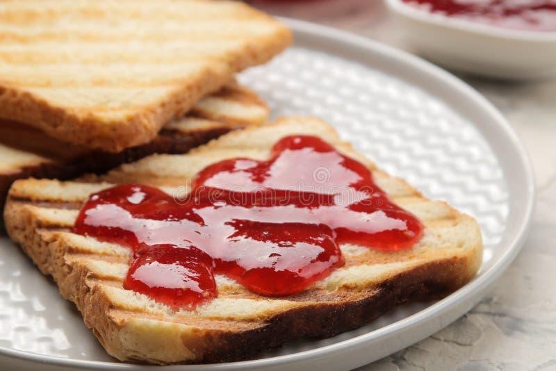 sitt fast rostat bröd stekte frasiga rostade bröd med rött driftstopp på en ljus konkret tabell panera upp skivor för korven för  royaltyfri bild