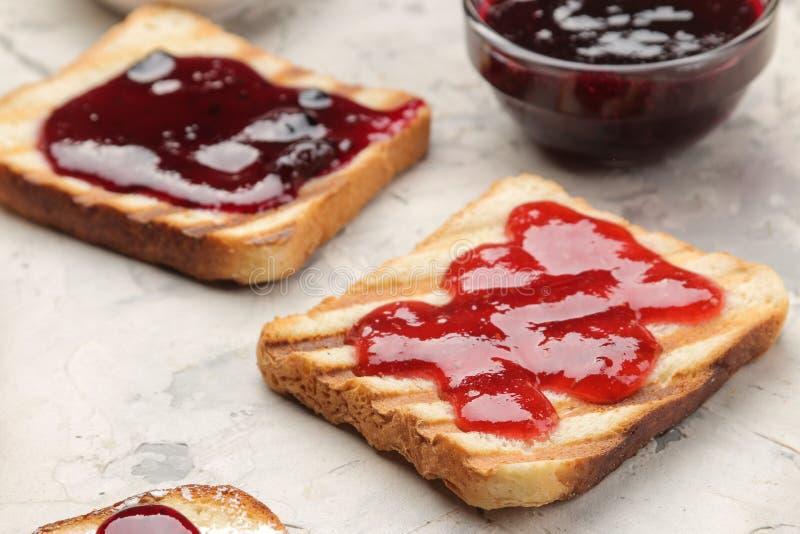 sitt fast rostat bröd stekte frasiga rostade bröd med rött driftstopp på en ljus konkret tabell panera upp skivor för korven för  royaltyfri fotografi