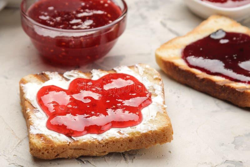 sitt fast rostat bröd stekte frasiga rostade bröd med rött driftstopp på en ljus konkret tabell panera upp skivor för korven för  royaltyfria foton