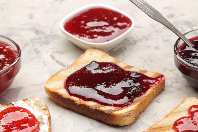sitt fast rostat bröd stekte frasiga rostade bröd med rött driftstopp på en ljus konkret tabell panera upp skivor för korven för  arkivfoton