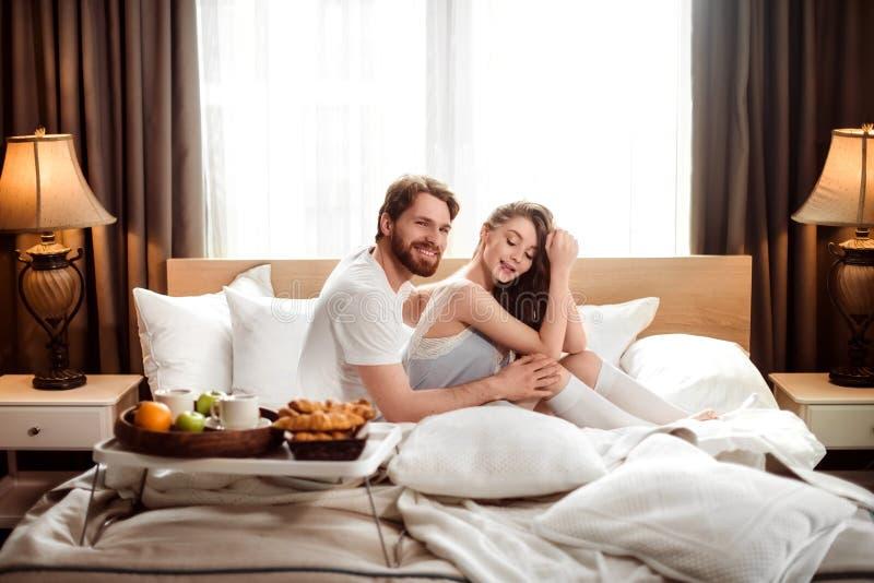 Sitt tillsammans i bekväm säng i hotellrum, le skäggiga mannen som den är lycklig att spendera fri tid med hans kvinnliga vän arkivbild