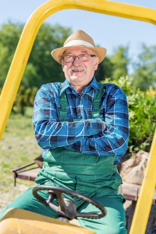 Sitta för hög man som är stolt i hans traktor, når att ha odlat hans lantgård royaltyfri fotografi