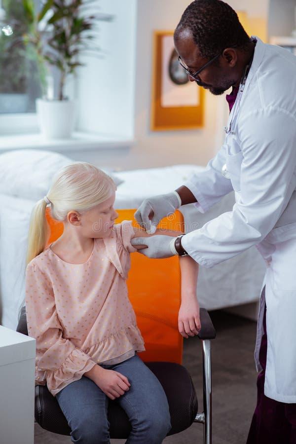 Sitta för skolflicka och hållande ögonen på doktor som desinficerar hud efter injektion arkivbilder
