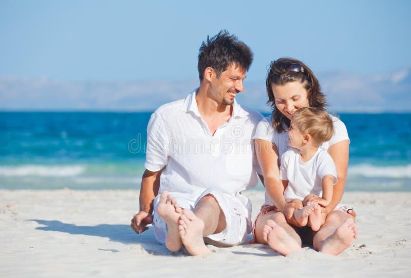 sitta för strandfamilj som är tropiskt royaltyfri bild