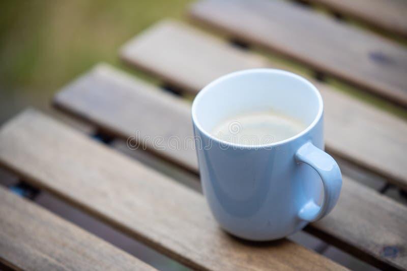 Sitta i trädgården tidigt på morgonen med en varm kopp kaffe arkivfoto