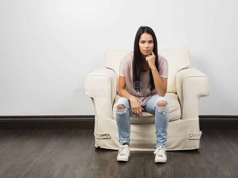 Sitta på en vit soffa arkivfoto