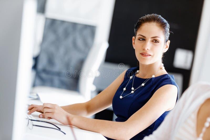sittande arbetare för attraktivt skrivbordkontor royaltyfria bilder